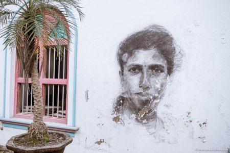 Zdjęcie przedstawia rysunek uśmiechniętej kobiety na ścianie domu w Kerali
