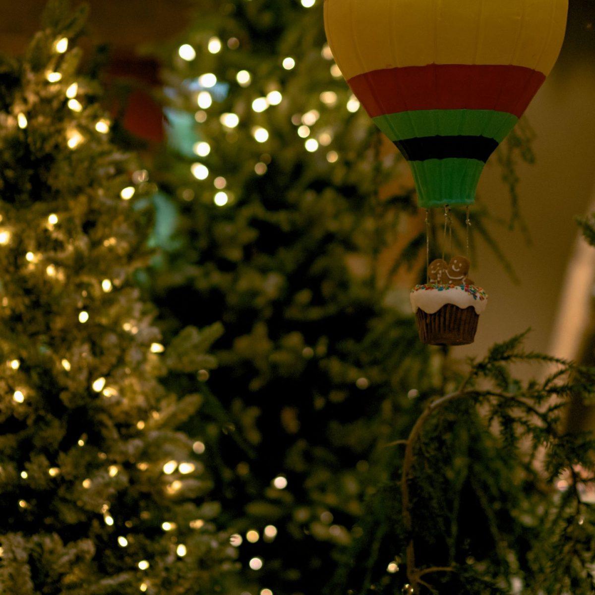 Balon na ogrzane powietrze, w gondoli dwa pierniczki, a za nimi świąteczna choinka