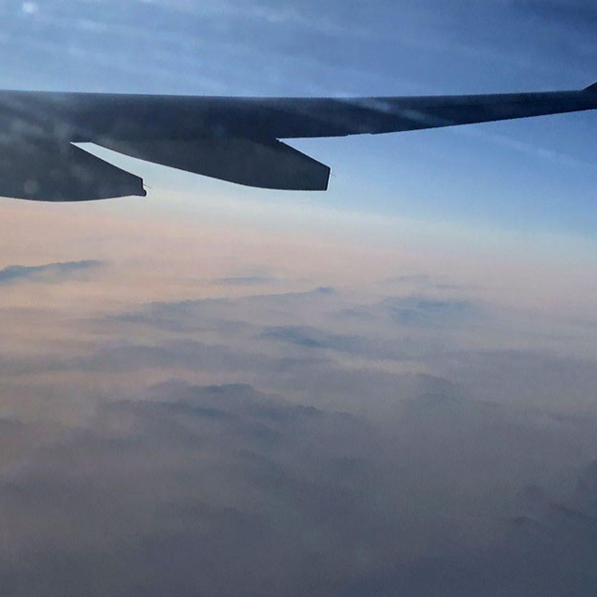 skrzydło samolotu pod którym widać wysokie góry