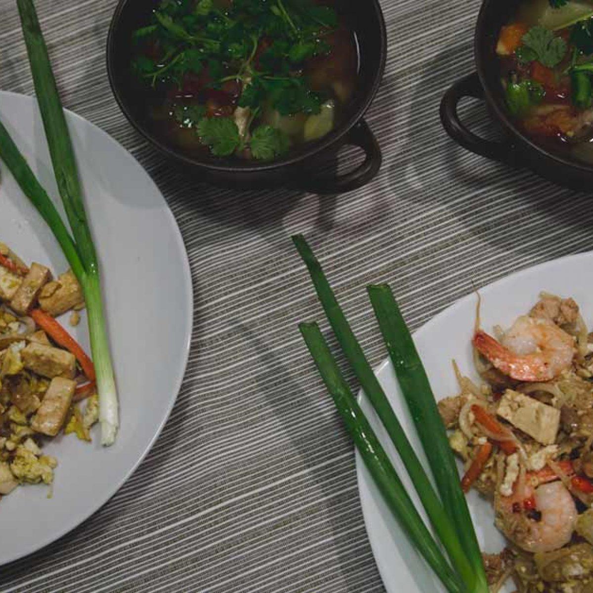 Stojące na stole dwie miseczki z zupą Tom Yum oraz dwa talerze z Pad Thai