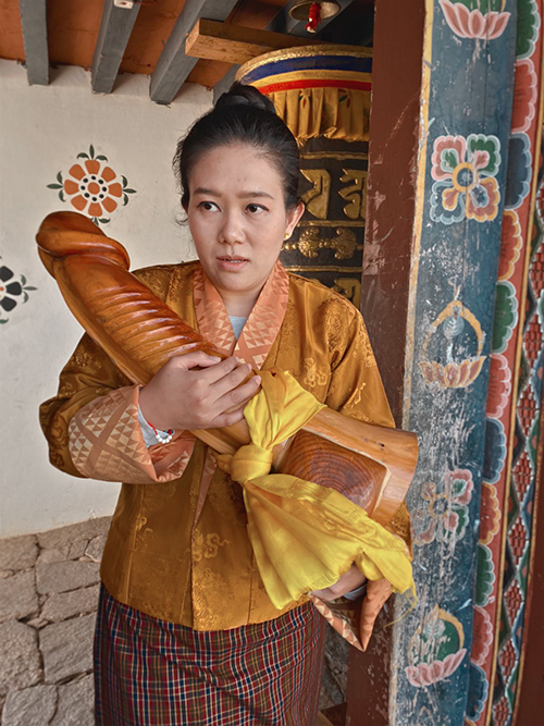 Bhutańska kobieta trzymająca w rękach olbrzymiego, drewnianego penisa